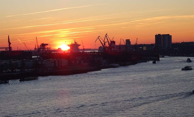 Sunset with crane skyline and ships on river Elbe at port of Hamburg