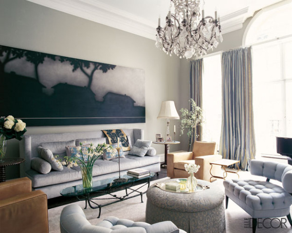 living room with different shades of blues and greys crystal chandelier and leather chairs
