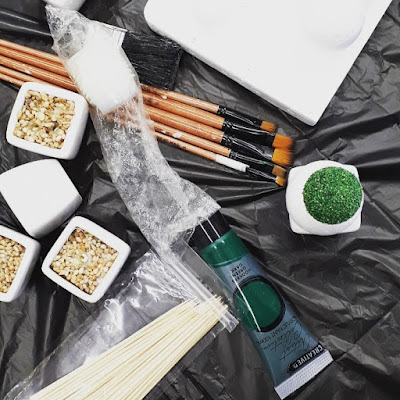 Flat lay of green paint, brushes, miniature platers and skewers against a black plastic background.
