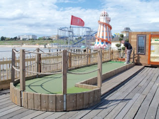 Playing minigolf on Clacton Pier in 2011. The helter skelter isn't there anymore. The rollercoaster is though