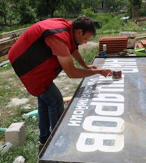 Ivan painting our school sign