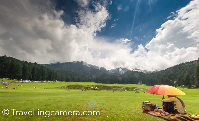 A visit in an year to Khajjiar  has made me click less photographs and rather experience different weather there. I was in Khajjiar during monsoons and this is probably the best season to experience lush green landscapes all around. Khajjiar, at times, is not accessible during winters because roads get closed due to snowfallThis is the first view of Khajjiar lake when you are coming from Dalhousie. This is the point where you should start looking for parking slot. Road condition is usually not very good during monsoons. Maintaining roads in hills is very challenging, but still Himachal has been aggressive in maintaining it's roads. Especially roads in tourist regions.During Monsoons, it's very important to keep umbrella with you, even if sun is shining and there is no patch of clouds. This change in minutes and hence very unpredictable. Our day started with clear sky and by the time we reached Khajjiar it started raining heavily. Fortunately we were carrying few umbrellas and borrowed one from our cab driver.While it was raining, we took a table in one of the restaurants around Khajjiar Lake. It was lunch time and we thought of utilizing this time and had lunch. I am forgetting the name of the place where we had lunch and it was good Punjabi food.A few kilometers ahead there is a temple with this huge Shiva idol. Now let me share a very useful tip. If you came to Khajjiar from Dalhousie in a bus and want to go back in bus only. Reach this place 30 minutes back. Usually there are lot of folks who board bus in Khajjiar and it becomes very challenging to get in. Since this temple is a stop before Khajjiar, there is good probability to get in comfortably and also find a seat. There are 2 buses from Khajjiar to Dalhousie between 1pm to 3pm.So if you come early in the morning, the timings would suit you.These days paragliding  is also quite popular activity around Khajjiar. One flies from a surrounding hill. You need to climb of the hill, so be sure about it. After flight, depending upon the flow of wind you can have a top view of Khajiar, but landing happens in village behind the shiva temple. I haven't done paragliding here so don't know the charges. Bir Billing is best place for Paragliding in Himachal Pradesh and I had that experience.Another view of Shiva from road connecting Khajjiar with ChambaMonsoon is a good time to taste local produce. Local cucumber is much tastier than what we get in cities through cold storage. During Monsoons, you would see lot of folks selling fresh fruit salad around Khajjiar and what can be best snack when travelling in himalayas.Clouds make this place more beautiful. I made some videos of clouds covering this place and going upwards to play in woods, but unfortunately we lost those videos due to card corruption. As I see some herbs vendor in above photograph, so let me warn you about a group of folks who sell you local herbs (don't know what that means and I never bought). But I have heard bad experiences of folks who dealt with these vendors. Please note that most of them are not local folks. and things they sell are not locally produced. They bring stuff from Jammu or Pathankot and sell to tourists. So if you can judge the originality of stuff being sold, go have a talk. Otherwise avoid even talking.  Pre-wedding shoots and post wedding shoots are getting popular in our country. And I noticed lot of couples here at Khajjiar with professional photographers. Some of these photographers roam around the lake and click photographs to hand-over in form of prints. Some of the photographers had come with couples, were indulged in finding appropriate location and guiding these couples for some unique shots.I also wanted to do a shoot with my model, but this time she was acting like celebrities. And even weather was not favoring us. So this time, I couldn't click much.Here is path outside the green meadows, which is used for horse riding. You can hire a horse to have a round of Khajiar or roam around the neighboring villages. I never took the other route where these folks promise to show village and apple orchards.  Carefully notice this photograph. Imagine the view when these clouds are slowing coming out of these forests. This was the best moment and experience at Khajjiar.There are lot vendors selling toys for kids. Urvi also wanted few but settled at one, which didn't reach home safely :). We had long day, so that was expected... I like some of these things at tourist places which provide opportunities for local folks. Some selling these toys, few making fruit salad and others selling juicy bhuttas. And all these things are also available at reasonable costs if you compare with prices quoted in bigger cities like Delhi. And it's not about money, it's more about purity and love of these local folks.This was shot when I was just leaving for Chamba. These colorful baloons in front of these green landscapes looked awesome. Over the years I have seen this place transforming, in good as well as bad ways. Local authorities don't allow people to play any kind of sport on these lawns but there areNames of horses around Khajjiar are very interesting :) ... Romeo, Chetak etc..  If you intend to stay around Khajjiar, there are 3 reasonable options - HPTDC hotel, HPPWD Guest-House and Forest Guest-House. Apart from there are there are various private properties.