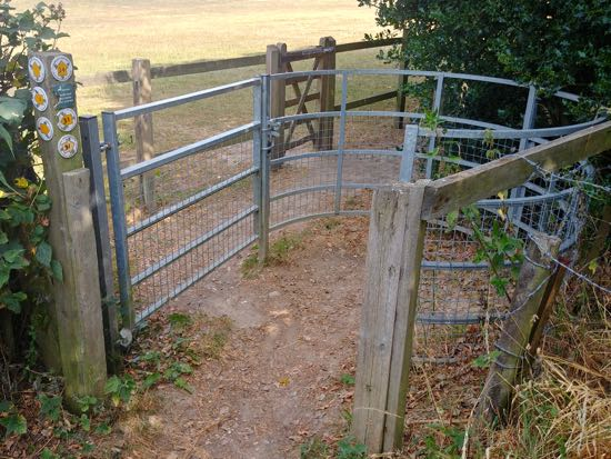 Go through the metal gate and then through the wooden gate on your left Image by Hertfordshire Walker released under Creative Commons BY-NC-SA 4.0