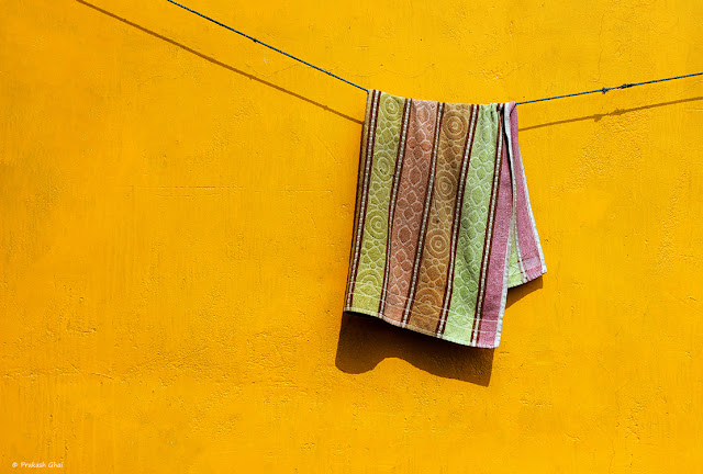A Minimalist Photograph of a Towel Drying On A Clothesline In India on a Yellow Wall.