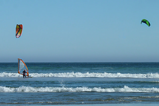 Kite surfers and wind surfer share water time...