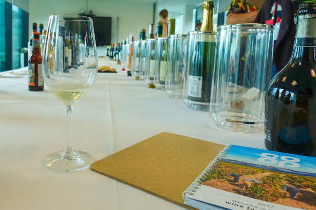 A co-op tasting guide and wine glass in the foreground and 2 lines of wine bottles in the background