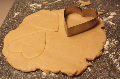 sugar cookie dough rolled out with a heart shaped cookie cutter in the dough, and several hearts already cut out