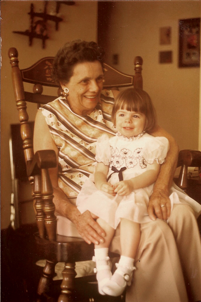 image of me as a toddler, wearing a white dress, sitting on my grandmother's lap in a rocking chair