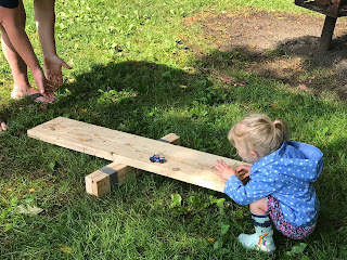 toddler girl playing with wooden board in grass at Sioux City Tinkergarten