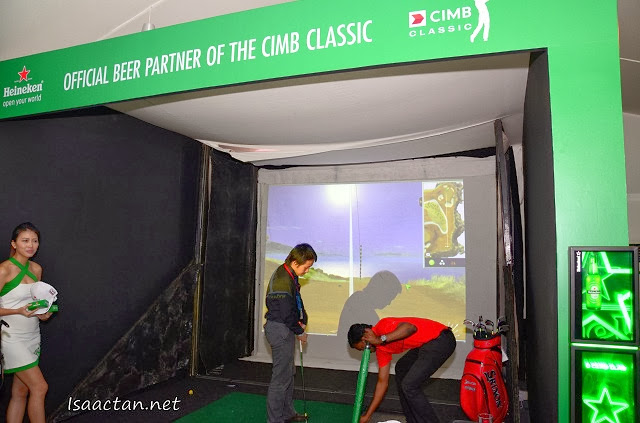Guests having a go at the Heineken Golf Simulator