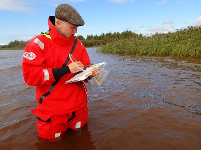 Mies kirjoittaa seisten reisiä myöten vedessä pelastautumispuvussa