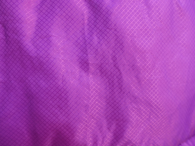 Material of purple sleeping bag with pattern of small squares.