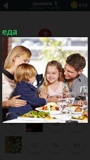 За столом сидит вся семья, перед ними приготовленная еда в тарелках