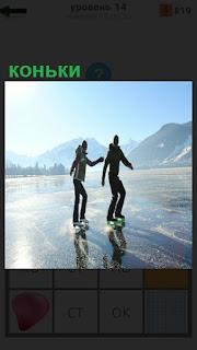На ледяной поверхности водоема парень с девушкой катаются на коньках
