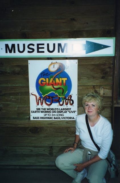 woman kneeling in front of sign for giant worm exhibit