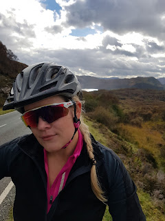 moody highland sky woman in oakley sunglasses with road bike