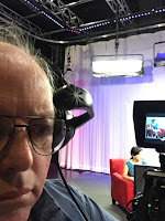 In the TV studio besides a camera, headset on head with the set in view through the camera viewfinder.