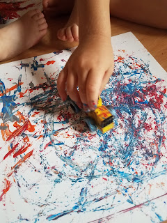 Toddlers painting with cars