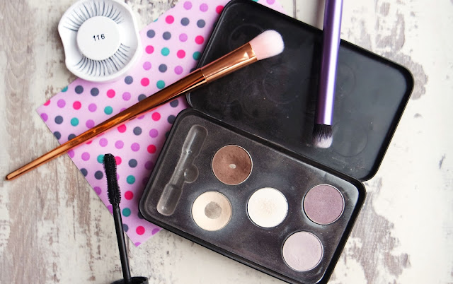 a black palette containing white, beige, brown, lilac, and purple eyeshadows. Mascara, false eyelashes, and makeup brushes surround it.