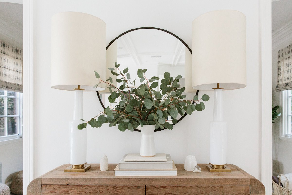 Eucalyptus, round mirror, and lamps on rustic wood console table