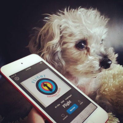 Murchie lounges on a fuzzy white pillow, his head raised and in three-quarter profile. A pale-skinned hand holds a white iPod parallel with his chin. The cover of Flight appears on the iPod's screen and features the black silhouette of a boy brandishing two guns and wearing a feather in his hair. The boy appears against a bullseye with yellow, red, blue, and black rings radiating out from the centre.