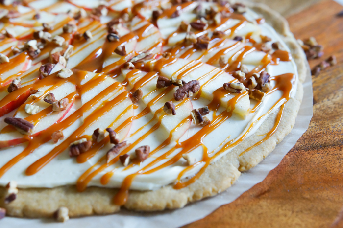 Honeycrisp Caramel Apple Pizza recipe: a spiced cookie crust, cream cheese spread, caramel sauce, toasted pecans, and of course, Honeycrisp apples.