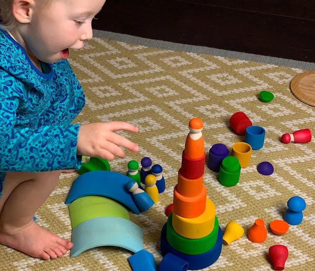 Toddler building a tower with colourful Grimms wooden pieces