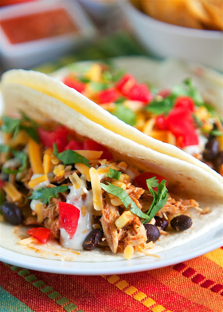 Slow Cooker Chicken Tacos - only 5 ingredients! chicken, salsa, taco seasoning, corn and black beans. Great in taco shells or on top of a salad. We ate this two days in a row! Such a great quick and easy Mexican recipe! The whole family loved it!