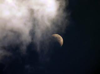 A cloud rolls toward the moon.