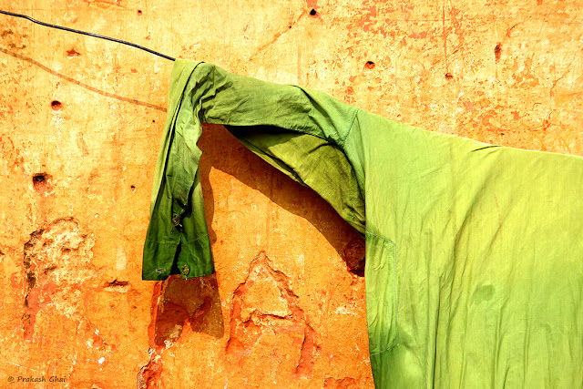 A Minimalist Photo of a Lucky green shirt drying on a clotheslines in India