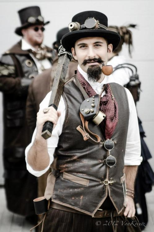 A man dressed in steampunk clothing carrying a wood club wrapped in barbed wire. Top hat, goggles, leather waistcoat, ascot, gas mask, trousers