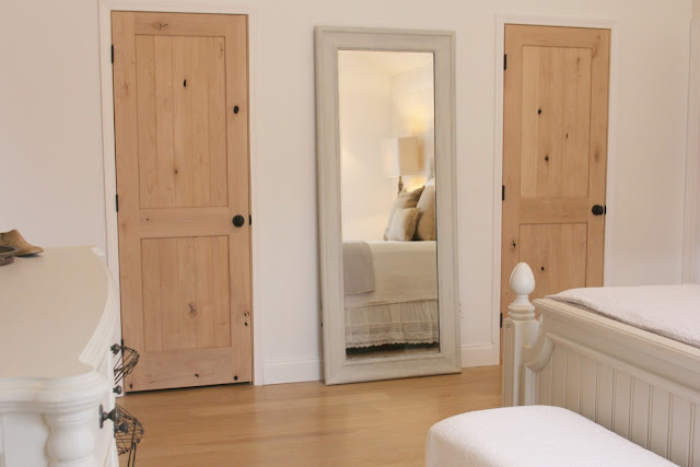 rustic alder wood doors in master bedroom with modern farmhouse style at Hello Lovely Studio's fixer upper