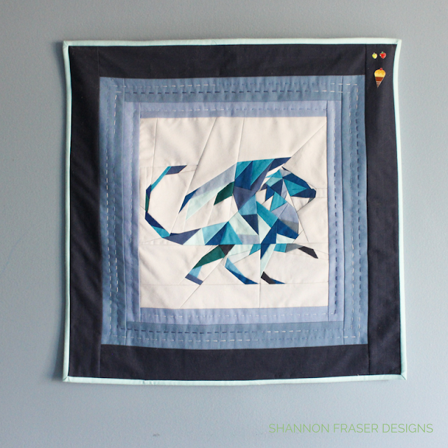 Geometric Quilted Dragon | Foundation Paper Piecing | Shannon Fraser Designs | Kona Cotton | Blue Solids | Quilting Technique | Modern Quilting | Hand Quilted | Aurifil Thread 12wt Varigated Blues Storm at Sea