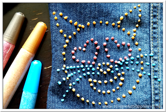 Easy cat emoji on denim made with Glitter Fabric Paint Pens  |  3 Garnets & 2 Sapphires