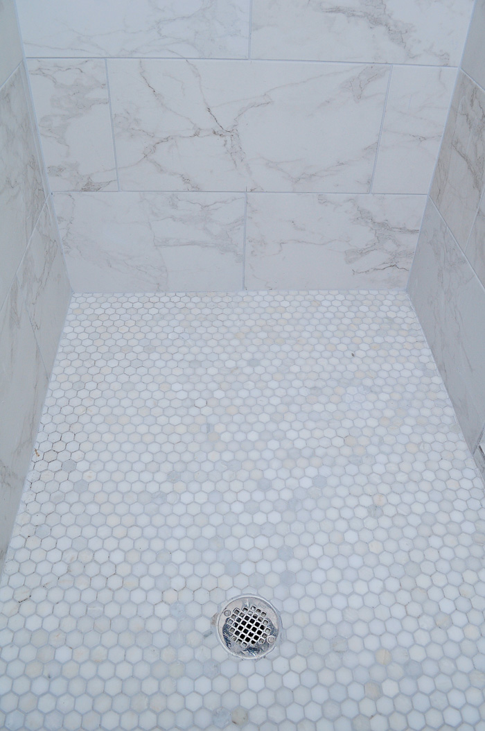 Marble hex tile shower floor paired with marble look tile in a master bathroom.