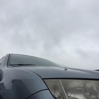 Graues Auto vor grauem Himmel
