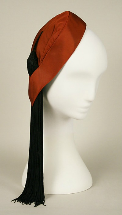 Red Charles James Hat with black tassel from 1952 displayed on mannequin head