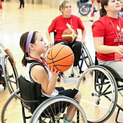 Young disabled girl in a wheelchair holding a basketball getting ready to make a shot during a wheelchair basketball game.