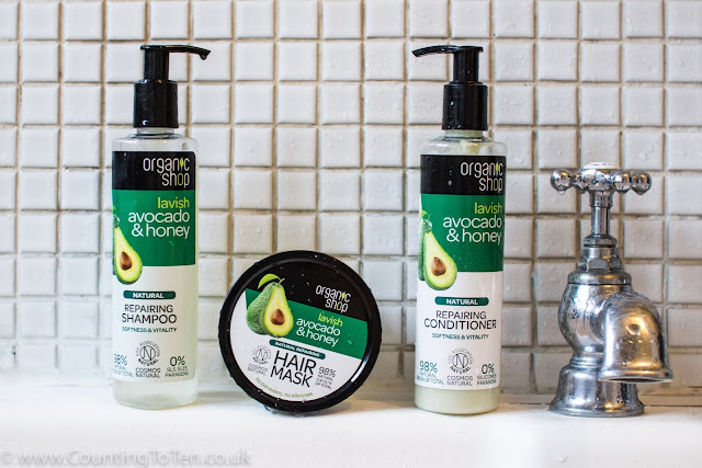 The Organic shop shampoo, conditioner and hair mask on the side of the bath next to a tap