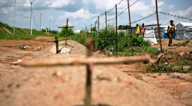 People walk on the other side of barbed wire where makeshift graves were placed in the Jebel area in Juba on July 22, 2016. By Charles Atiki Lomodong (AFP/File)  Addis Ababa (AFP) - South Sudan on Friday accepted the deployment of a regional intervention force after escalating violence put a fragile peace deal in danger, the head of the East African bloc IGAD said.