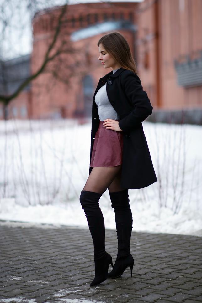 Czarny elegancki płaszcz, bordowa skórzana spódniczka i zamszowe długie kozaki