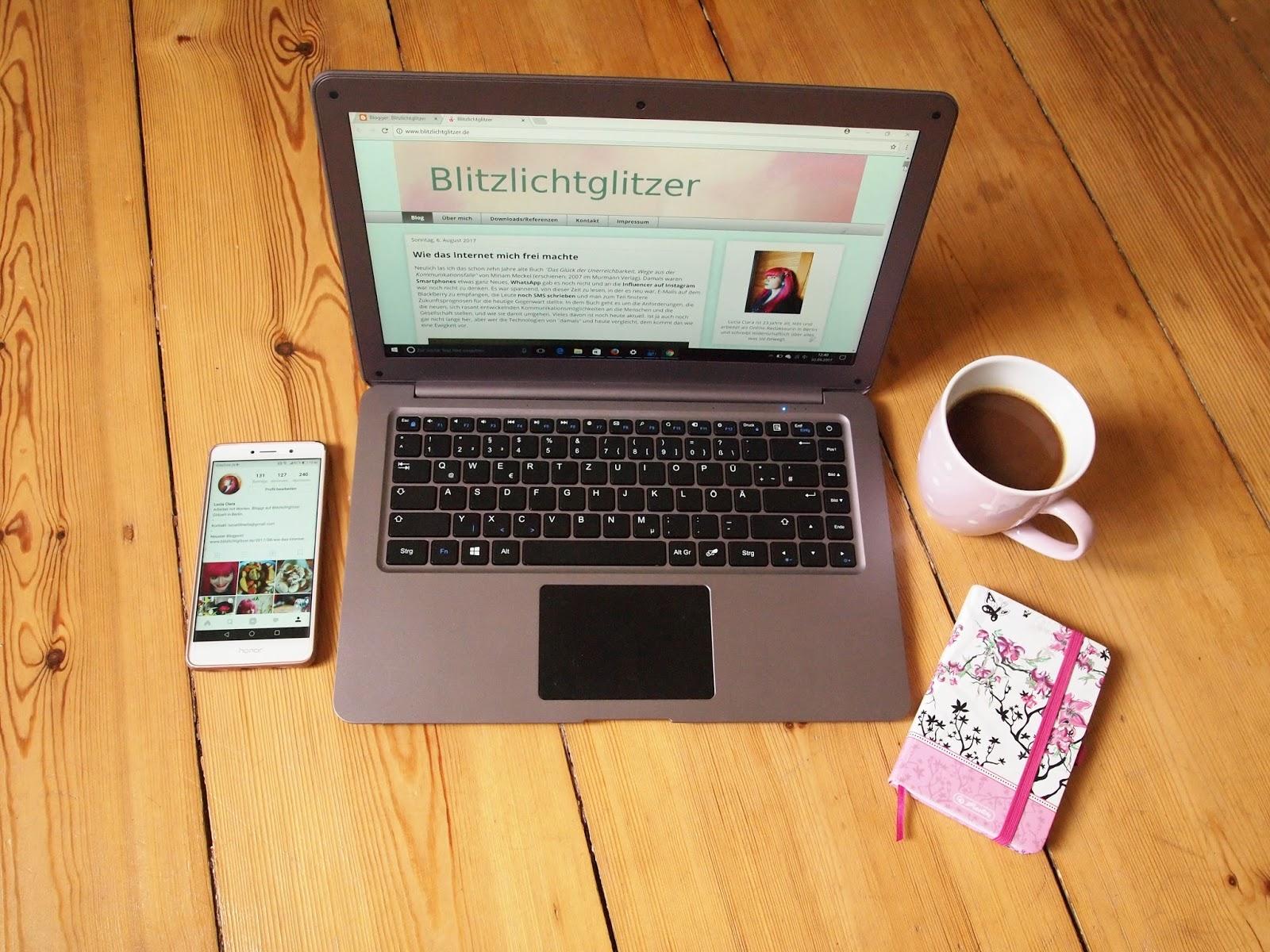 Laptop mit geöffneter Blitzlichtglitzer-Seite, Handy, rosa Notizbuch und rosa Kaffeetasse mit weißen Punkten stehen auf Holzdielenboden