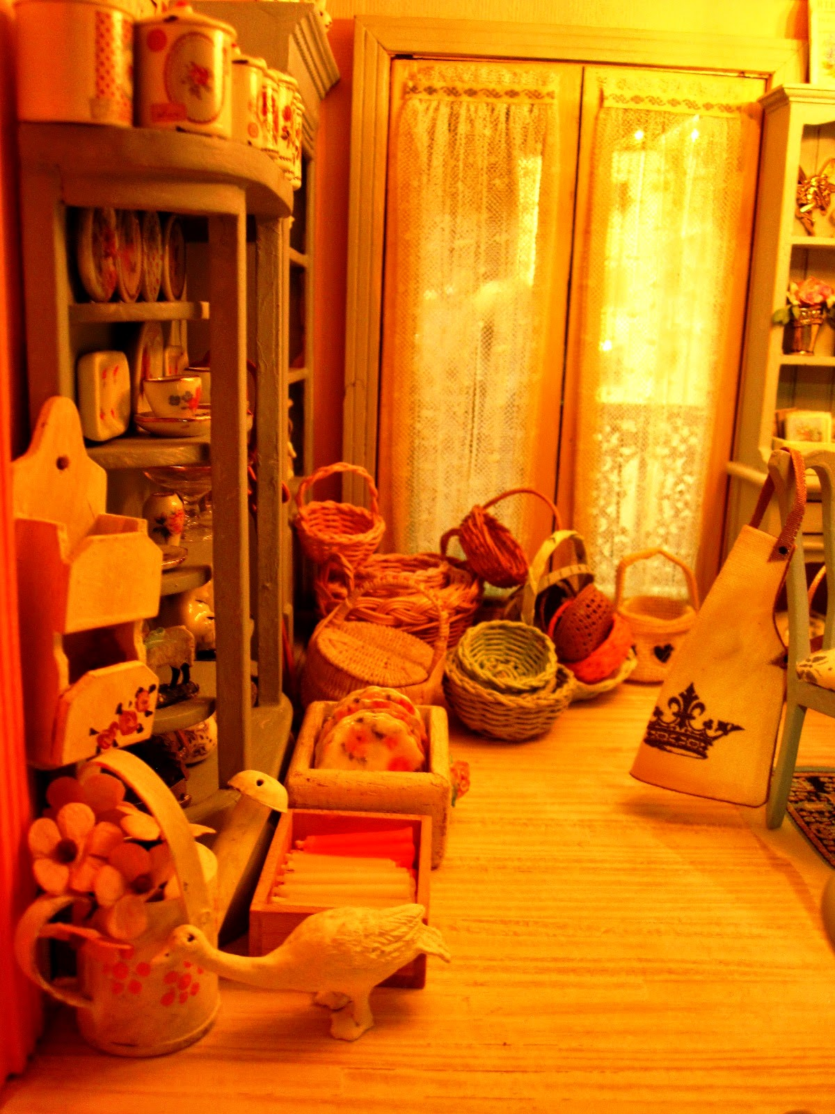The left-hand side of the first floor of a modern miniature shabby chic shop, with a range of canisters and baskets on display.