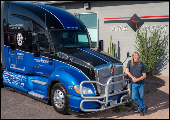 Kelly Lindsey stands with the Stewart Transport Truckers Against Trafficking Everyday Heros 2019 Kenworth T680
