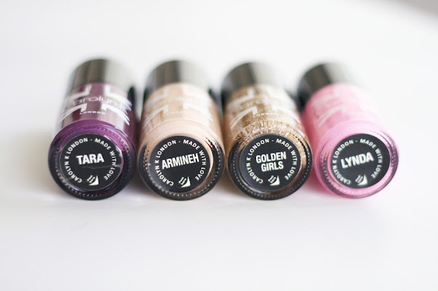 Nail paints in purple, nude, gold sparkle and pink