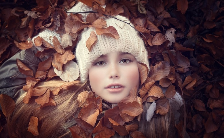pretty woman with hat surrounded by leaves illustrating winter skin care