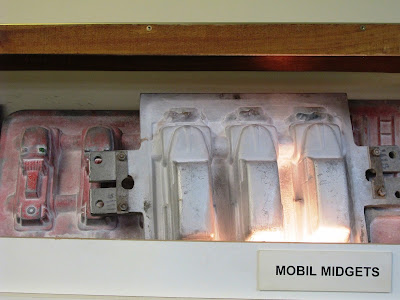 Moulds for sandcasting toy cars on display.