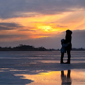 Parent hugging child on a beach at sunset