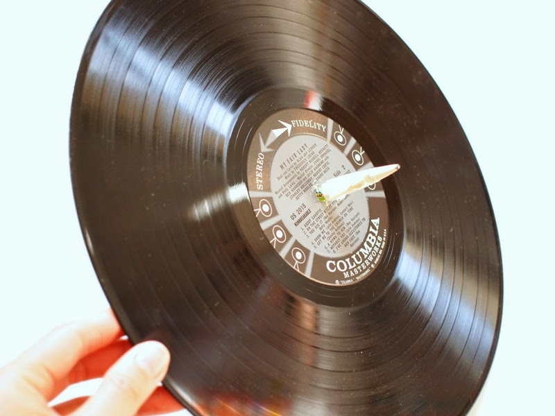 poke a pencil through the record to make it spin