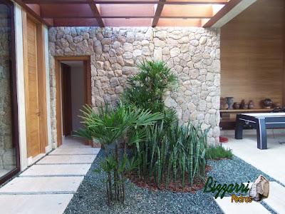 Revestimento de pedra na parede, com pedra moledo, em jardim de inverno em residência em Piracaia-SP.